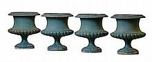 A set of four Continental green painted cast iron garden urns