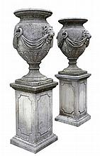 A pair of french carved limestone urns on pedestals, early 20th century