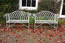 A pair of white painted metal garden seats, loosely in the George III style