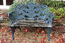 A cast and painted metal fern and blackberry pattern garden seat