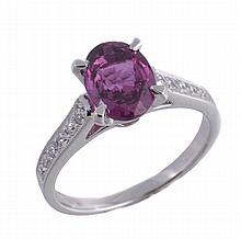 A purple sapphire and diamond ring, the oval cut