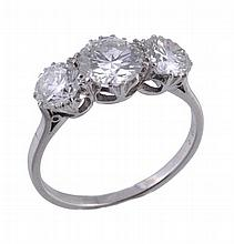 A diamond three stone ring, the central brilliant