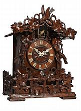 A Black Forest carved wood cuckoo table clock Attributed to Johann Baptist Beha