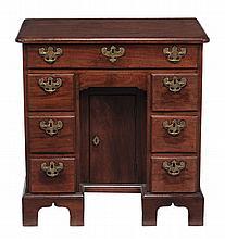 A George II red walnut kneehole desk, circa 1730