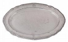 A George III silver shaped oval meat plate by John Wakelin & William Taylor, London 1789, with a gadrooned rim and engraved with an armorial and a crest, 41cm (16 1/4in) long, 1227g (39.45 oz). The arms of Bowles impaling Montagu quartering