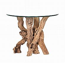 A glass top dining table, of recent manufacture, the base of natural tree stems
