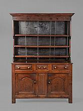 A George II oak dresser , circa 1740, with open shelves above three panelled...