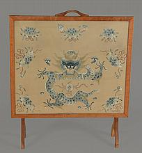 A light oak framed fire screen with a Chinese silk needlepoint panel