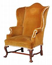 A walnut and upholstered wing armchair, in George