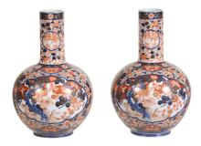 A pair of Japanese Imari bottle vases, densely painted with flowers and trees