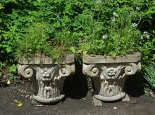 A pair of stone composition garden planters modelled as Ionic capitals