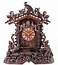 A Black Forest carved wood cuckoo table clock