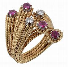 A ruby and diamond cross over ring, set with brilliant cut diamonds and...