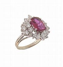 A ruby and diamond cluster ring, the oval cut ruby estimated to weigh 1