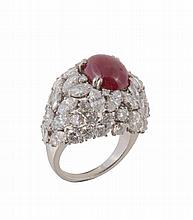 A French ruby and diamond cluster ring, the central oval cabochon ruby claw...