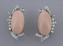 A pair of diamond and coral ear clips, the oval cabochon coral panels within...