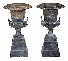 A pair of cast iron twin handled garden urns, of