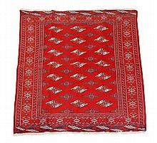 A Bokhara carpet, the madder field decorated with
