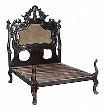 A French carved and ebonised hardwood bed frame, circa 1890, 221cm high