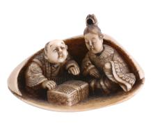 An Ivory Netsuke depicting a man and a woman sheltering within a large clam...
