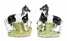 A pair of Staffordshire pottery models of piebald horses, mid 19th century