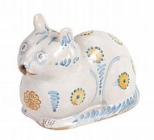A tin-glazed earthenware cat flask, naturalistically modelled as recumbent cat