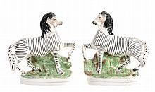 A pair of Staffordshire pottery models of zebras, mid 19th century