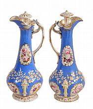 A pair of Staffordshire porcelain 'Rococo revival' ewers and stoppers