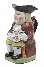 A Staffordshire pearlware Toby jug and a cover , circa 1810