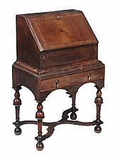 A George II walnut bureau , circa 1740, the book-matched fall opening to an...