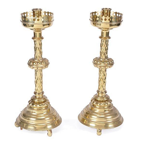 A pair of brass candlesticks in the Gothic style,