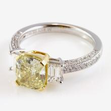 Platinum Ring with 2.01ct Cushion cut yellow and 2 trapezoid white diamonds.