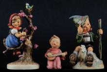 Three (3) Goebel Hummel Figurines Including: Mountaineer #315. Signed. Small Chip On Hat, Some Wear To Paint and Crazing On Bottom Otherwise Good Condition, Together With Apple Tree Girl. Signed. Good Condition and Angel Serenade Nativity Figurine. Signed. Good Condition. Tallest Measures 6-1/4 Inches Tall and 3-1/4 Inches Long. Shipping $20.00