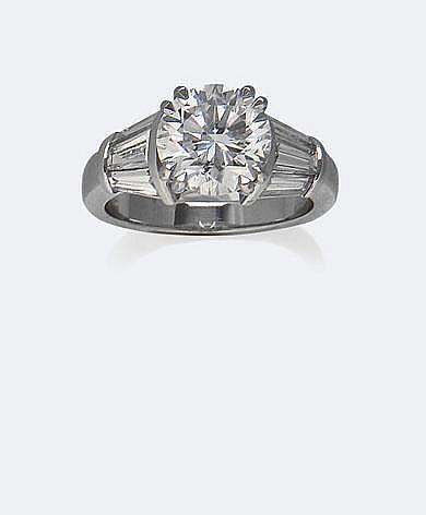 BAGUE SOLITAIRE en or gris, ornée d'un diamant taille brillant, 2,92 carats certifié E. S I 2 par le laboratoire HRD serti entre deux lignes de diamants taille baguette, total : 1,50 carat environ. Taille : 53 - Poids : 7,04 g brut.
