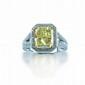 BAGUE en or gris, ornée d'un diamant de taille rectangulaire Fancy Yellow pesant 5 cts entouré de diamants, la corbeille et l'épaulement entièrement sertis de diamants. Poids: 10,8 g Le diamant accompagné d'un certificat GIA attestant : couleur Fancy