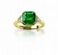 BAGUE en or jaune, ornée d'une émeraude taille émeraude à pans coupés, 4 carats environ entre deux diamants triangulaires en sertissure.  Taille: 53  Poids: 5,65 g