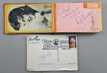 Autograph book with over 20 signatures including Roger Moore, Tony Curtis (signed postcard), Walker Brothers, Roy Orbison & others