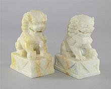 Pair of Chinese white stone carvings of dogs of Fo, the female with her cub, the male with a brocade ball. 20th Century.
