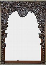 Late 19th early 20th century Indonesian carved hardwood mirror of arch form