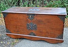 19th century Dutch colonial, Indonesian indigenous wood and gilt metal trunk with hinged top , the base with four wooden wheels