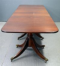 George III style mahogany three pillar dining table on splayed legs and castors,