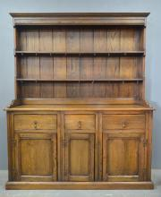 A 20th century oak dresser, the boarded open shelves over three drawers with cupboards below, 185cm high, 152cm wide