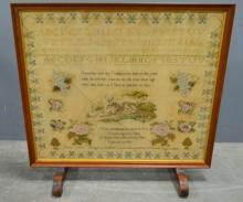 Sampler mounted as a fire screen with alphabet and a lamb, with verse , within a floral border