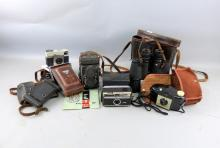 E Leitz 7x50 Binoculars, Yashica-Mat reflex camera, and four other cameras.