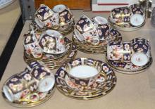 Seven Royal Crown Derby trios, and an extra plate, and six coffee cans and saucers,