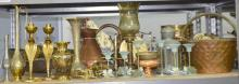 Quantity of old copper and brass and pewter to include candlesticks, plates, vases, displayed over two shelves.