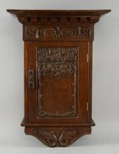 Arts & Crafts carved oak wall cupboard with floral decoration carved in relief, height 53cm, width 37.5cm, depth 21cm.