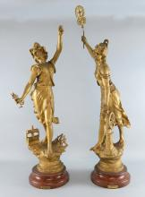 A pair of large French spelter figures representing L'electricite and La Vapeur,, gold painted on faux marble bases, The largest 85cm High.