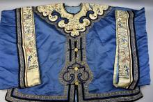 Chinese blue silk jacket, the collar and cuffs heavily embroidered with figures in a garden and flowers and foliage, length of back 63cm,