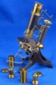 Brass and cast metal microscope in fitted mahogany case,
